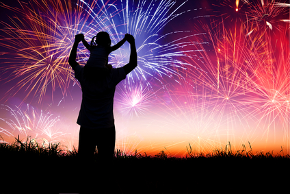 father with child standing on the hill and watching the firework